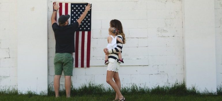 man holding a us flag on the wall of a house