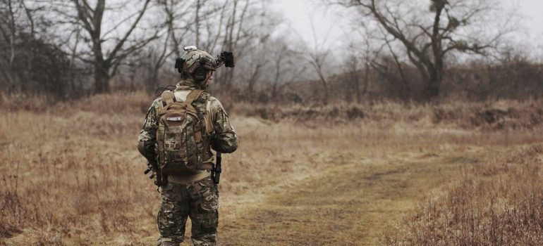 Man wearing a military uniform and walking through woods