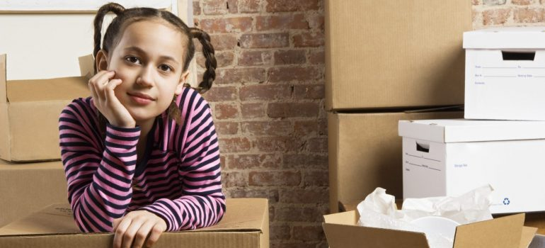 Girl with moving box, representing what to unpack first