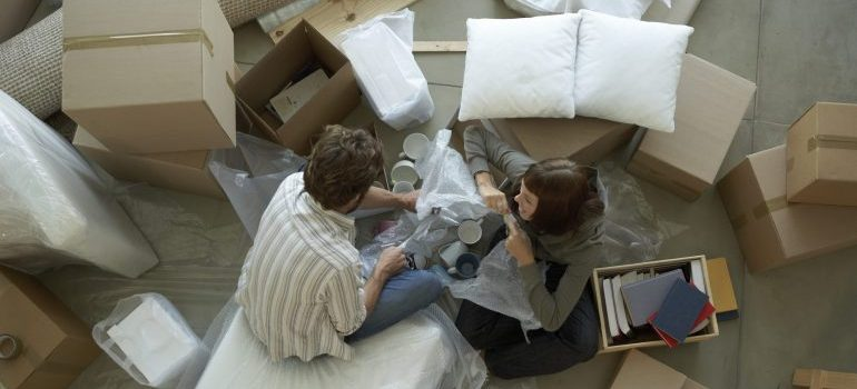 Couple surrounded by boxes packing, representing packing services