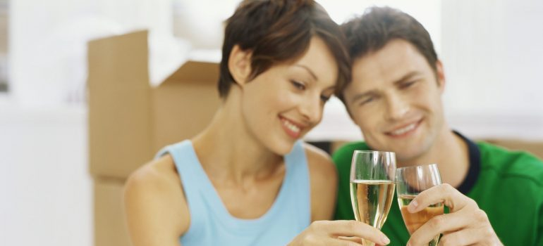 close-up of a young couple making a toast, representing how to de-stress after a move